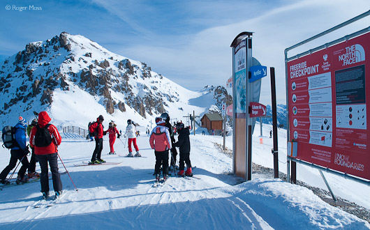 Skiers looking at piste map, Serre Chevalier