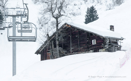 Chairlift passing traditional mountain chalet at Areches Beaufort, French Alps.