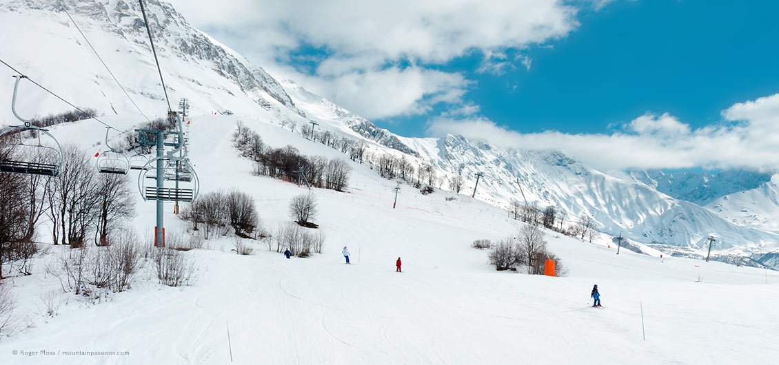 Wide view of family skiers from chair-lift, showing Albiez-Montrond ski terrain