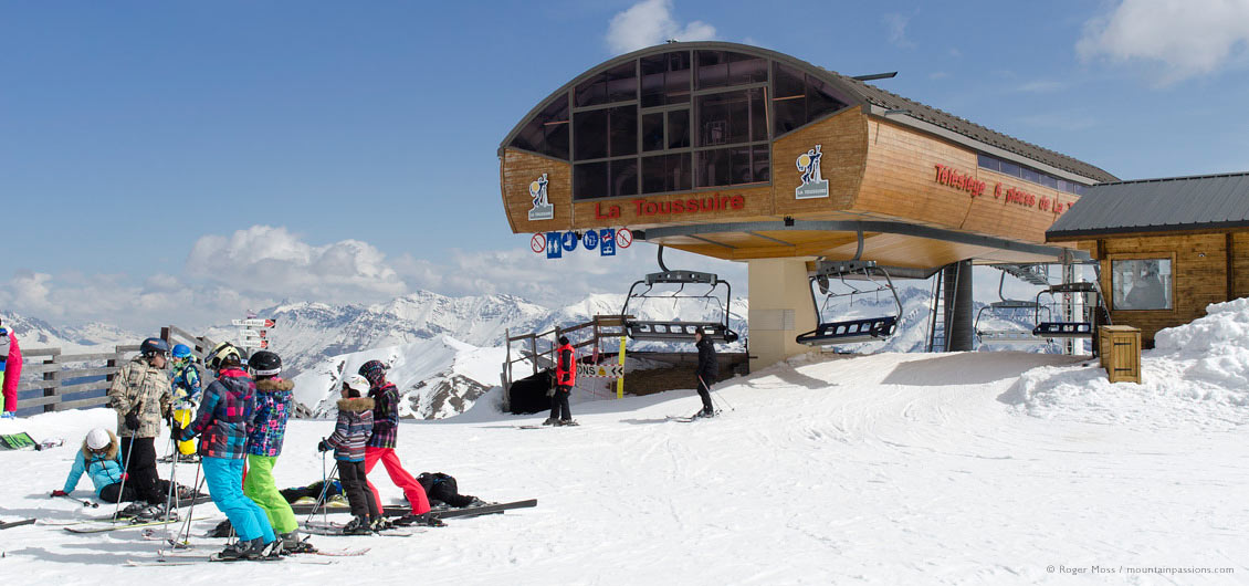 Group of skiers beside high-speed chair-lift at La Toussuire, Les Sybelles, Maurienne, French Alps.