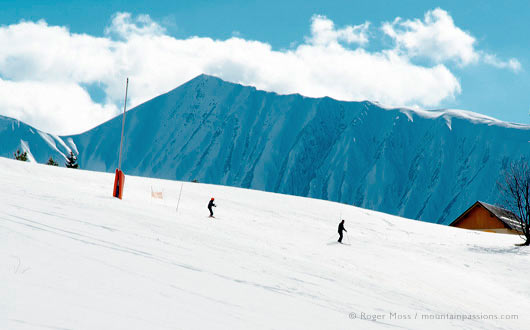 Two skiers on wide piste on sunny day
