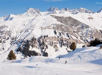 View of three skiers descending piste among rugged mountain scenery