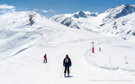 Skiers on wide open piste among snow-capped mountains, La Toussuire, French Alps
