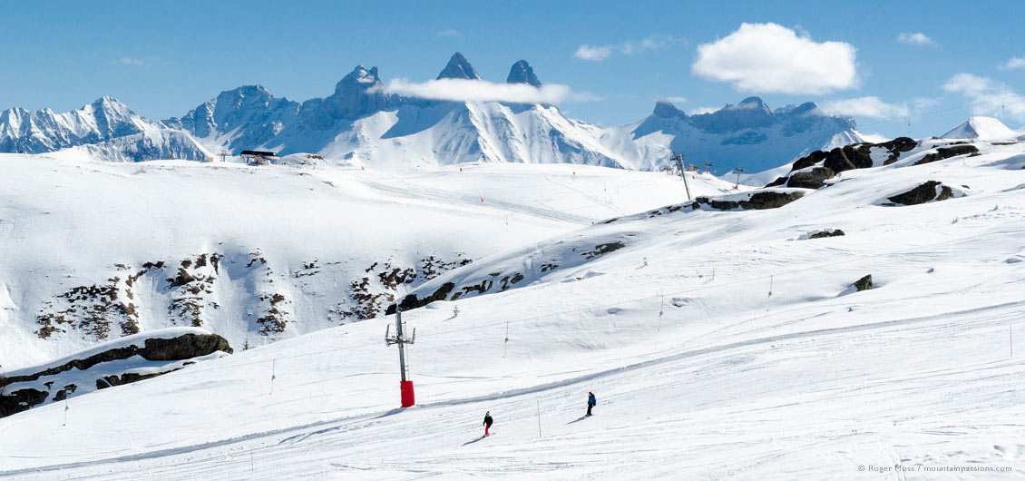 Long view of skiers on wide piste with distant peaks at La Toussuire, Les Sybelles, Maurienne, French Alps.