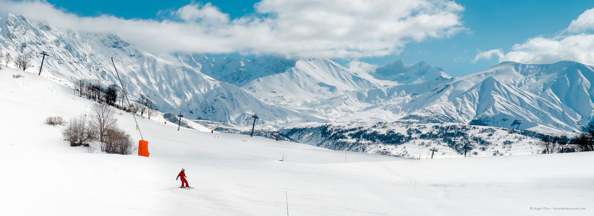 Wide view of child skier with big mountain backdrop at Albiez-Montrond.