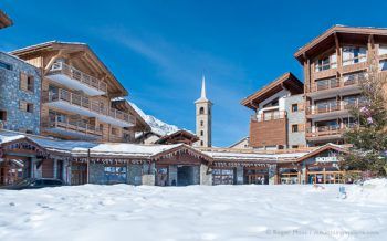 View across fresh snow to chalet-style ski village, with church spire in background