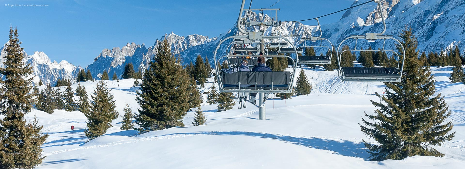 View from chair-lift of ski terrain with trees and mountains