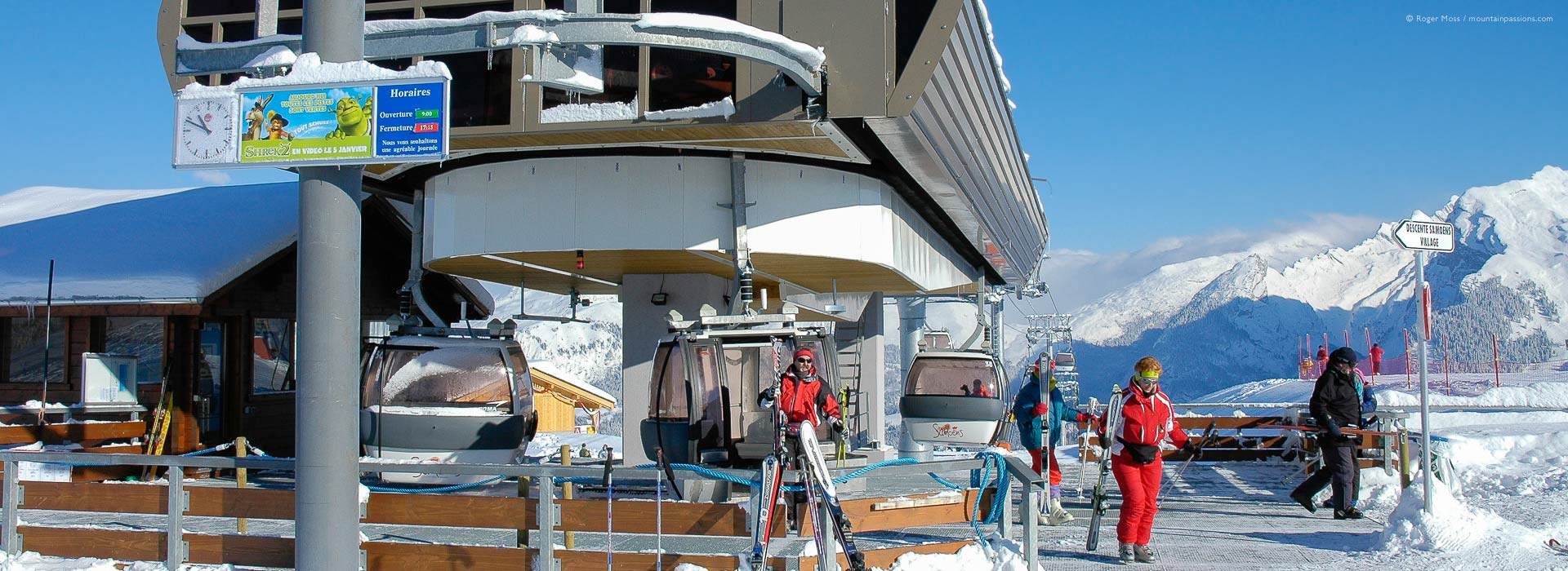 Skiers leaving top station of high-speed gondola ski lift