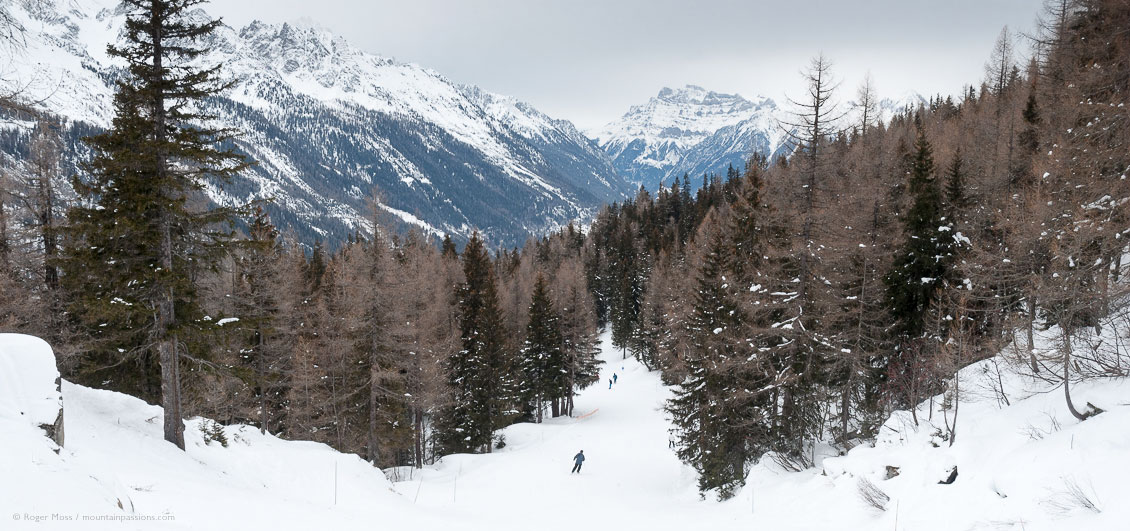 Wide view down ski piste, with forest and mountains above Vallorcine