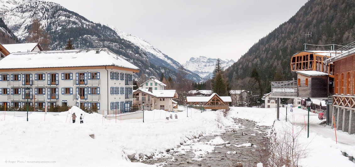 Wide view of village, showing ski apartments, river, gondola lifts and snow-covered valley