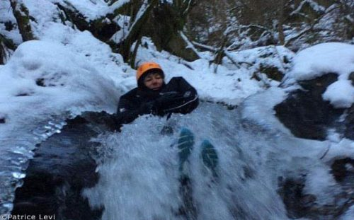 winter canyoning, person sliding down waterfall