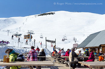 Skiers relaxing on sun terrace above Les 2 Alpes, with mountainside and chairlift