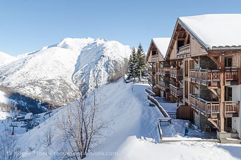 Exterior view of Goleon ski apartments, with mountains and ski lifts at Les 2 Alpes