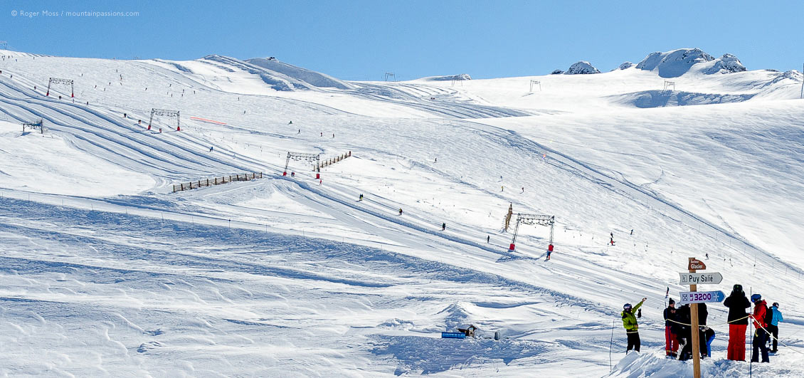 Long view of skiers at base of snow-covered glacier with ski-lift