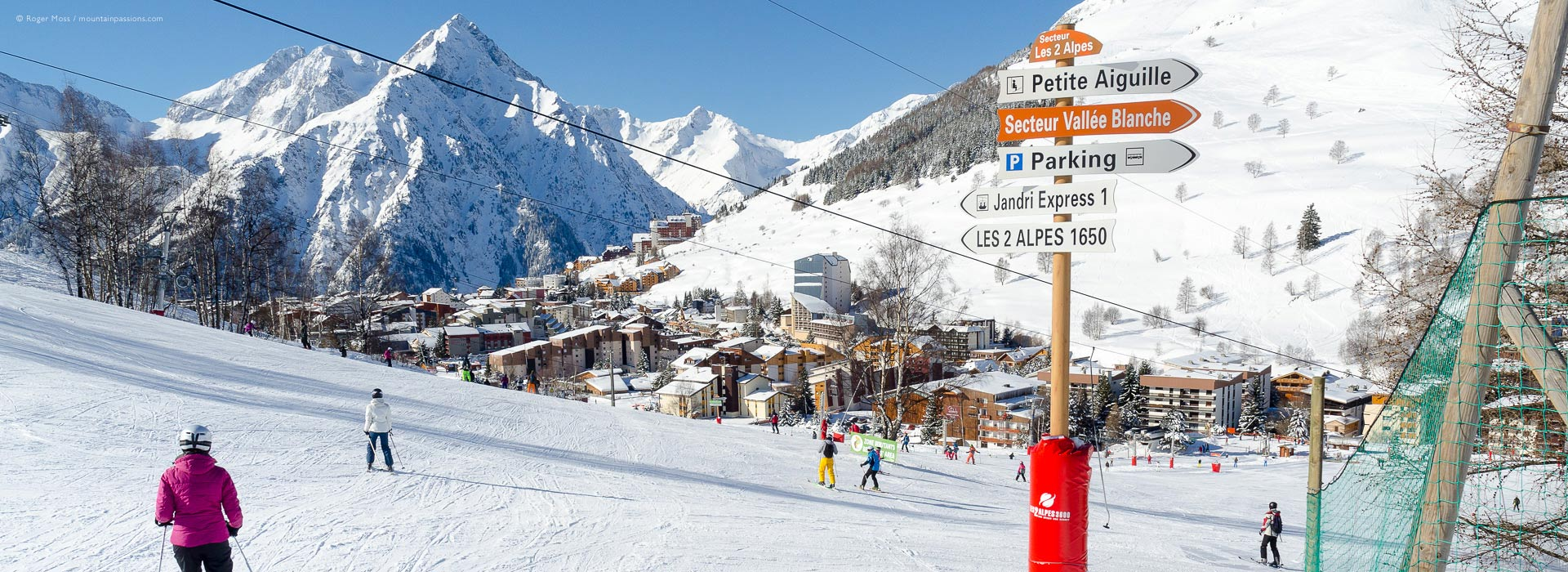 Wide view of skiers approaching ski lifts, with Les 2 Alpes ski village and mountains