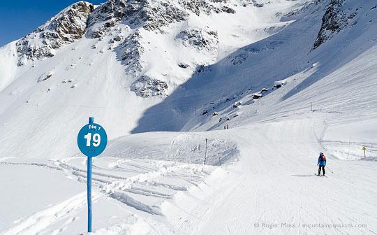 Skier on slow zone piste among wild mountain scenery at Les 2 Alpes