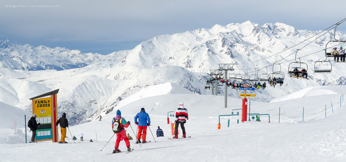 Skiers beside family fun area with big mountain view, at Les 2 Alpes