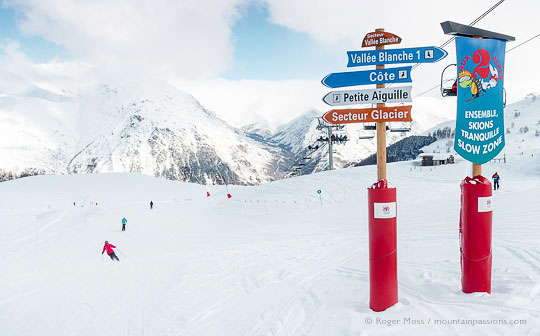 Wide view of mountainside with skiers passing signage at Les 2 Alpes