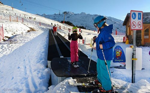 Young skiers on magic carpet ski lift, ESF ski school, Les Menuires