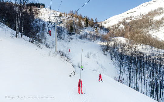 View from chairlift of skier on woodland piste at Les 2 Alpes.