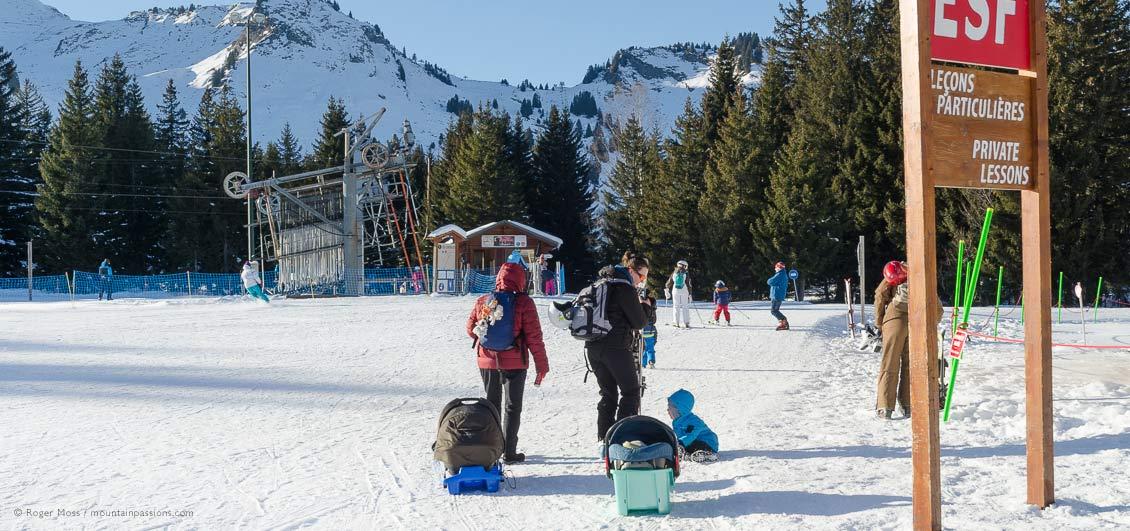 Young family walking to ski school area at Praz de Lys, French Alps.
