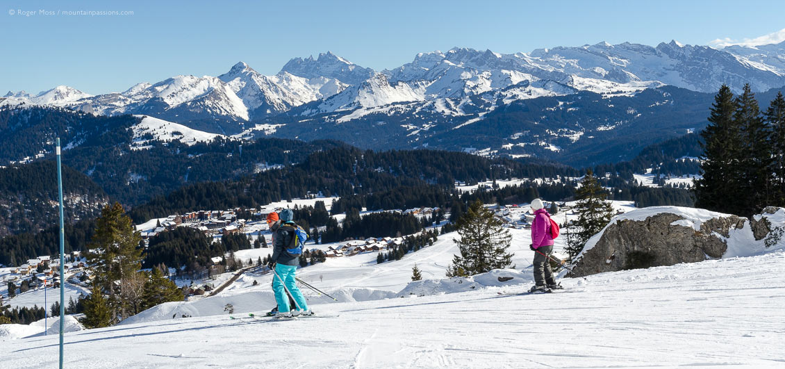 Group of skiers on gentle piste above village and forests at Praz de Lys, French Alps.