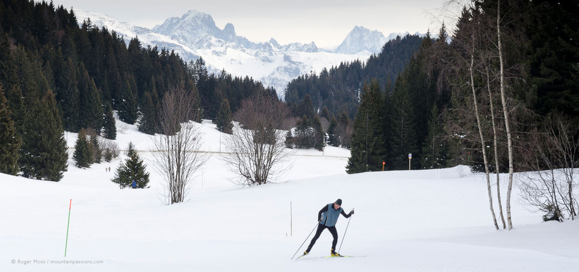 Wide view of cross-country skier with forests and mountains in background at Praz de Lys