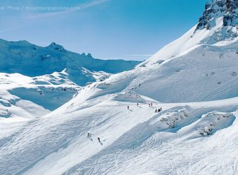 Skiers among big mountain scenery above Tignes