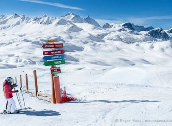 Skiers beside piste-signs at Val d'Isere, Espace Killy