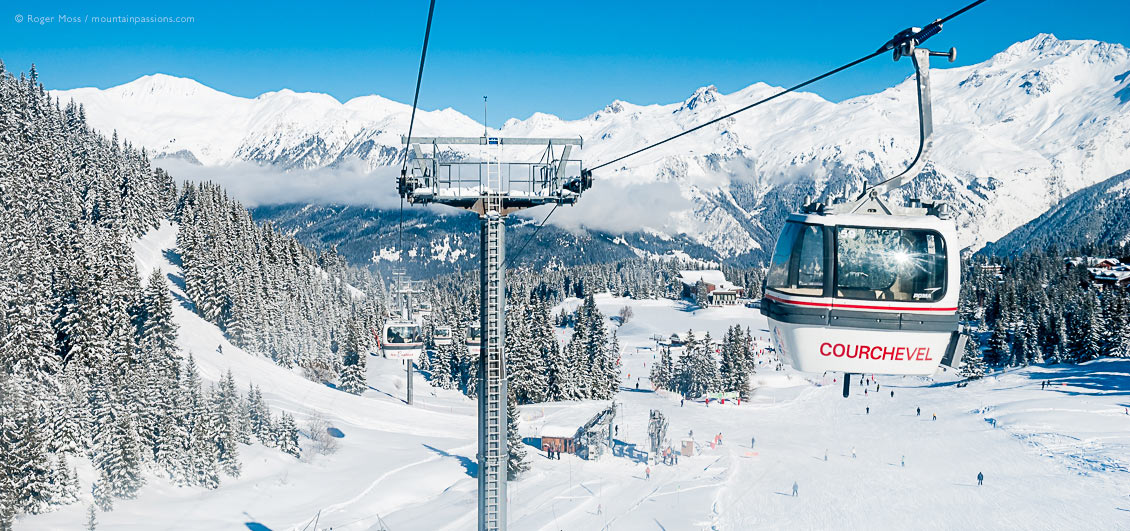High view of gondola lift with Courchevel 1850 ski village and snow-covered mountains