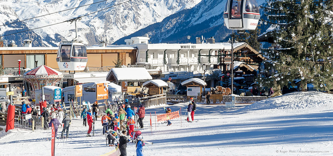 Skiers and gondola lift at Courchevel 1850 ski village, French Alps