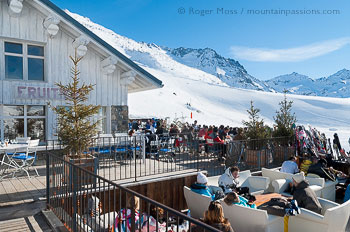 View of skiers relaxing on sun terrance at La Fruiterie, Val Thorens.