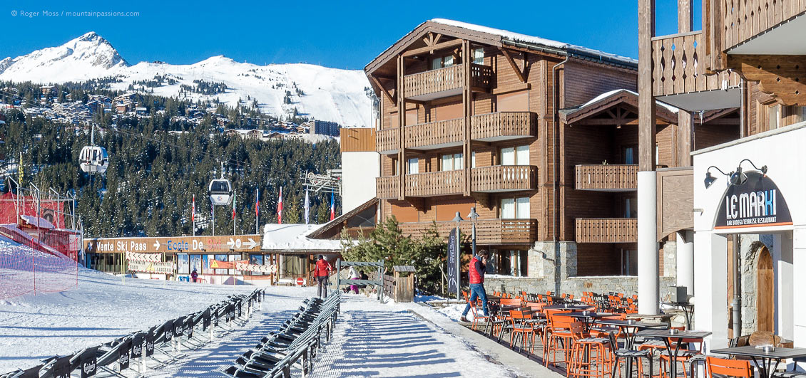 View of front-de-neige cafe terrace and gondola ski lift at Courchevel Moriond, French Alps.