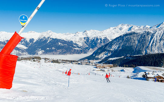 Wide view of skiers on piste heading for Couchevel 1850, French Alps.