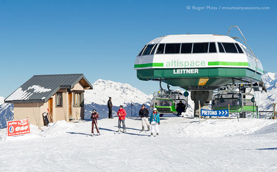 View of skiers leaving Altispace chairlift at Valmorel, French Alps.