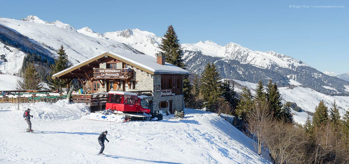 Two skiers passing mountain restaurant at Valmorel, Savoie, French Alps.