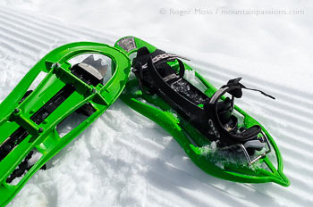 Pair of lightweight showshoes on snow, showing piste grooming lines.