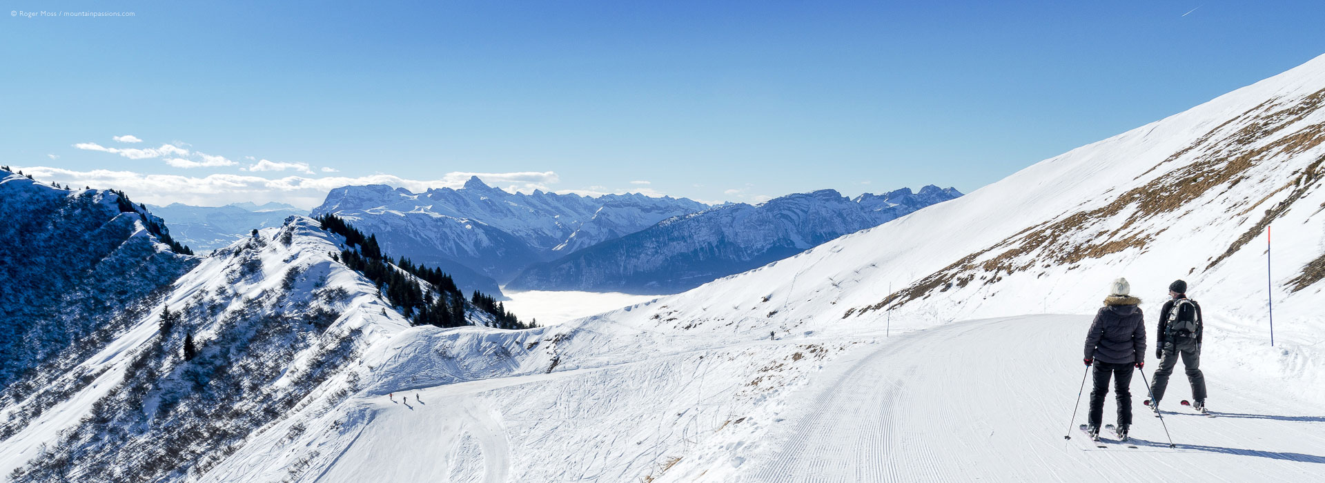 Wide view of two skiers on high mountain piste at Praz de Lys Sommand, French Alps.