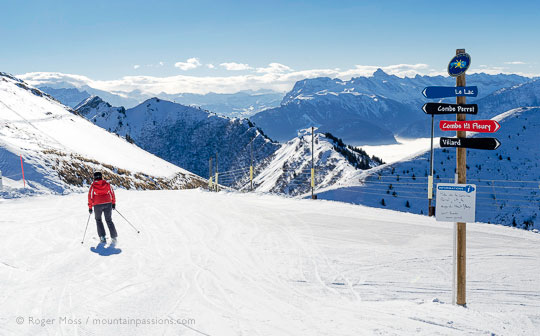 Skier starting Lac piste with mountain scenery above Praz de Lys, French Alps.