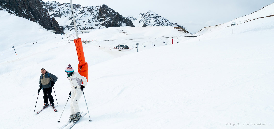 Skiers beside snow cannon at La Mongie, Grand Tourmalet, French Pyrenees