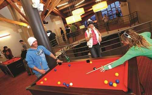 Young guests playing pool at a UCPA hostel