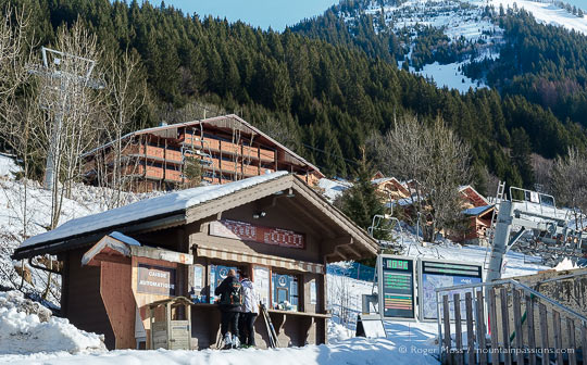 Skiers buying lift passes beside chair-lift, with chalets and mountainside