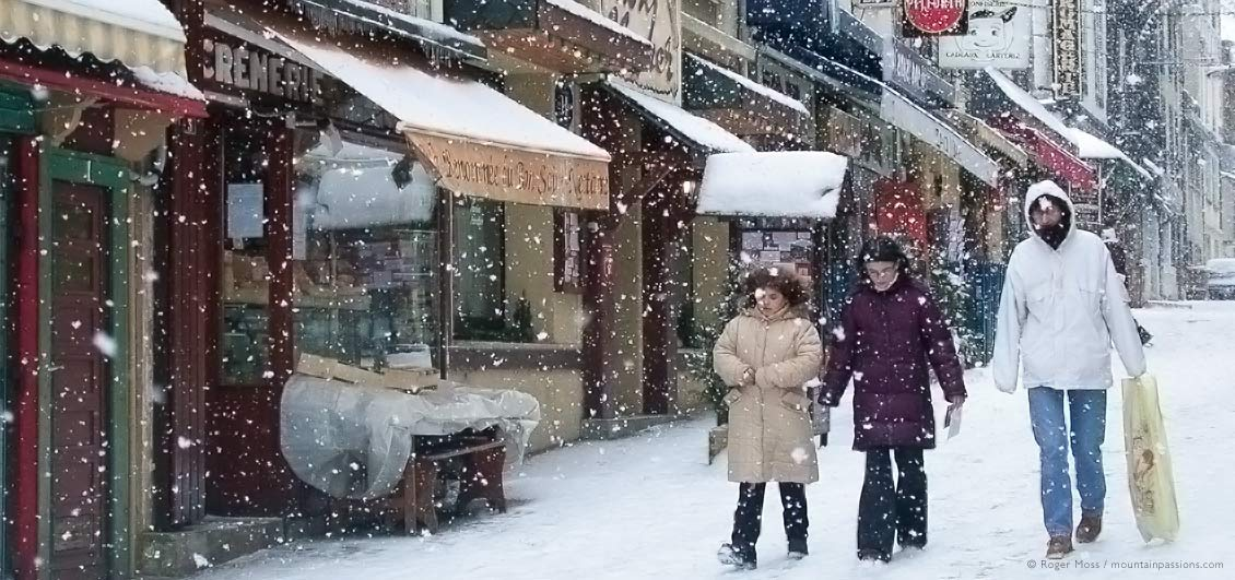 Family in falling snow at Le Mont Dore ski village, Auvergne, France.