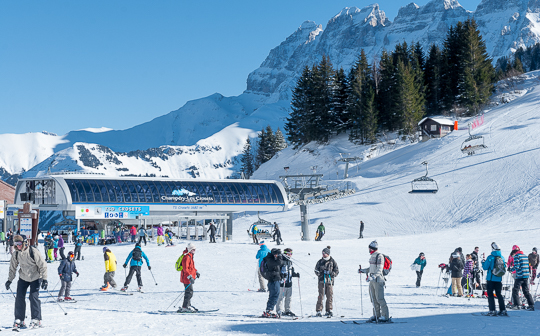 Skiers around big chairlift in wide valley at Les Crozets