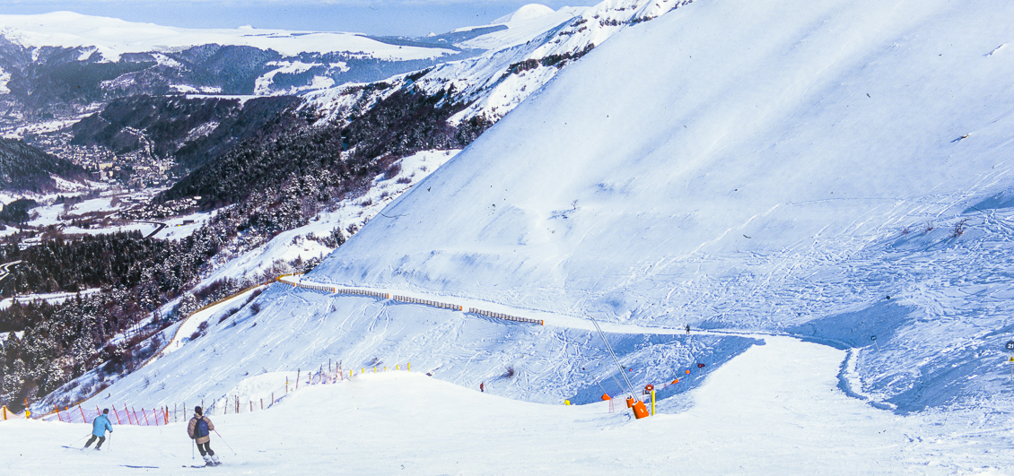 Two skiers on piste at Le Mont Dore, Auvergne, France.