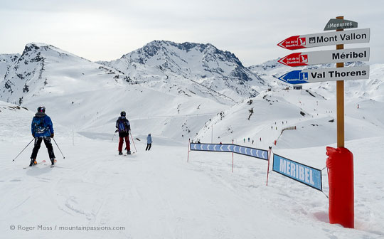 Skiers passing piste sign