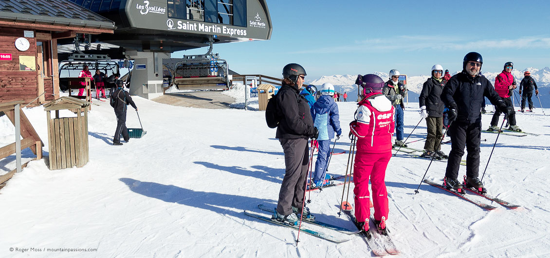 Skiers and ski instructor beside chairlift above Saint Martin de Belleville