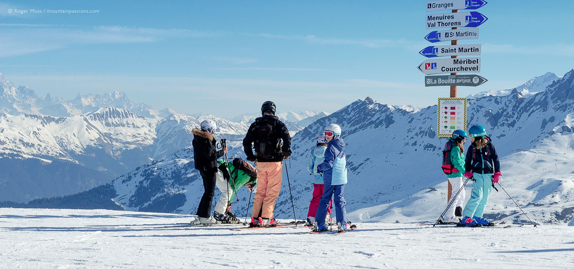 Skiers beside sign with mountains