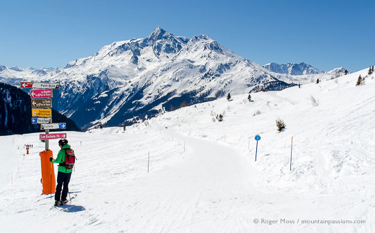 Skier beside piste signage with mountains