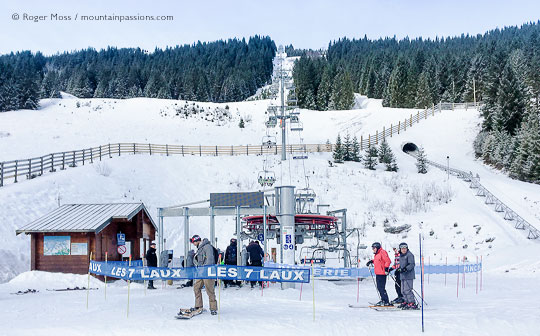 skiers joining chairlift at Le Pleynet, with snow-covered mountains